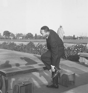 Martin Luther King retire ses chaussures avant de visiter le tombeau de Gandhi, à New Delhi, en 1959. (Associated Press)